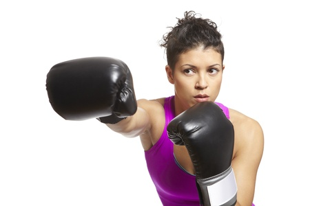 Young woman with boxing gloves throwing a punch in sports outfit photo