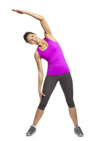 warm up: Young woman in yoga pose wearing sports outfit smiling on white background Stock Photo