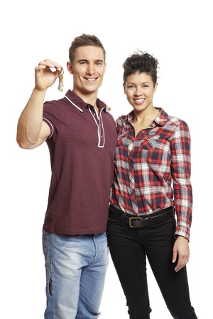 first time buyer: Young couple holding set of house keys on white background smiling