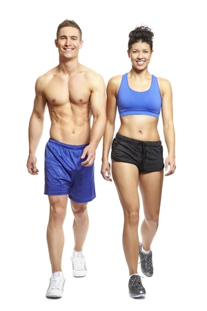 physical fitness: Young man and woman walking in sports outfits on white background smiling