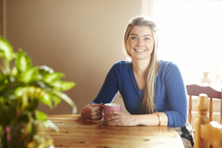 happily: Young woman sitting at table with hot drink smiling  Stock Photo