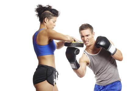 Jonge man en vrouw boksen sparring in de sport outfits op een witte achtergrond Stockfoto