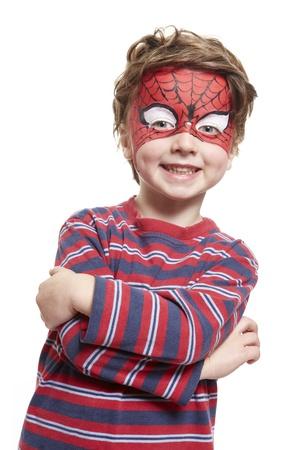 Jonge jongen met gezicht het schilderen spiderman lachend op een witte achtergrond Stockfoto