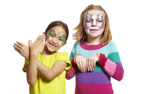 party outfit: Young girls with face painting of cat and butterfly smiling on white background Stock Photo