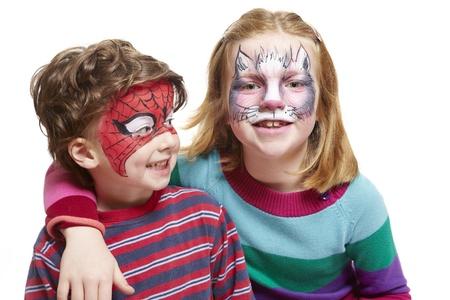 maquillaje infantil: Chico joven y una niña con pintura de la cara del gato y el hombre araña sonriente sobre fondo blanco