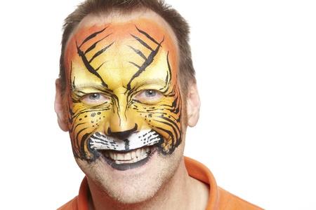pintura en la cara: Hombre con pintura de la cara del tigre sonriente sobre fondo blanco Foto de archivo