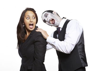 Man in dracula fancy dress costume biting girls neck on white background photo