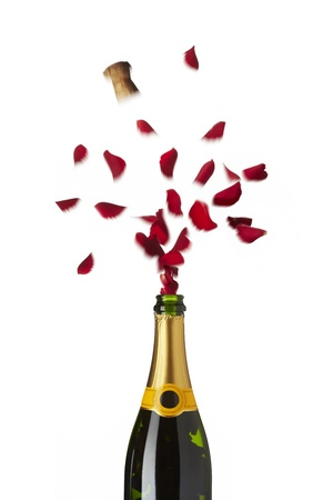 romantically: Bottle of champagne popping red rose petals with cork into the air on white background