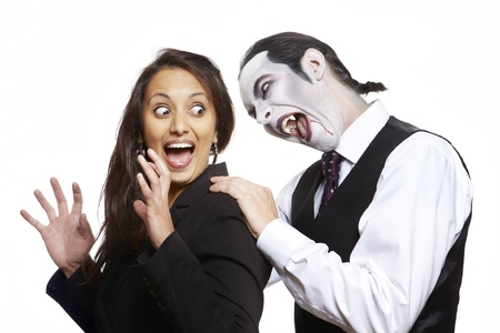 fearing: Man in dracula fancy dress costume biting girls neck on white background
