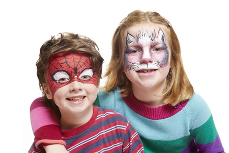 Young boy and girl with face painting of cat and spiderman smiling on white background Stock Photo