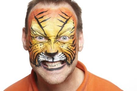 painting face: Hombre con pintura de la cara del tigre sonriente sobre fondo blanco Foto de archivo