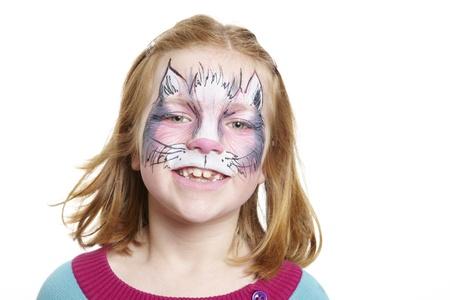 painting face: Chica joven con el gato pintura de la cara sonriente sobre fondo blanco Foto de archivo