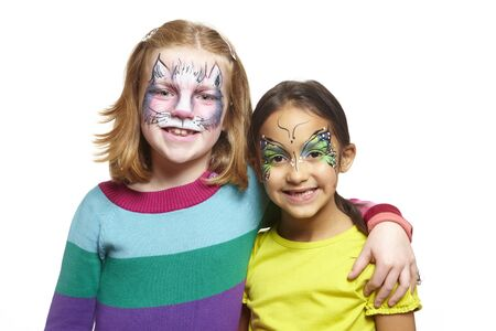 painting face: Young girls with face painting of cat and butterfly smiling on white background Stock Photo