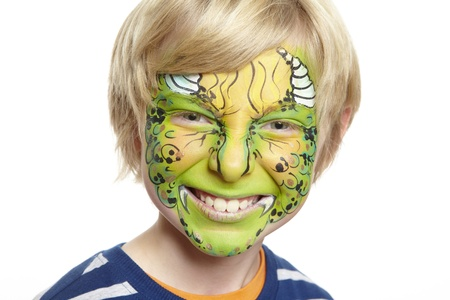 Young boy with face painting monster smiling on white background photo