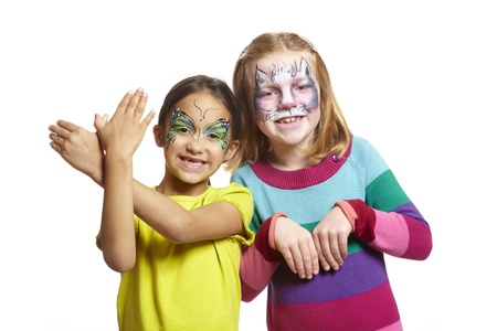 Young girls with face painting of cat and butterfly smiling on white background Stock Photo - 17531243