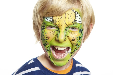 painting face: Young boy with face painting monster smiling on white background Stock Photo