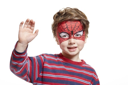 Young boy with face painting spiderman smiling on white background photo