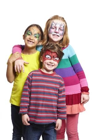 pintura en la cara: Chico joven y dos muchachas con pintura de la cara del gato, mariposa y hombre araña sonriente sobre fondo blanco