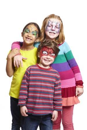 party outfit: Young boy and two girls with face painting of cat, butterfly and spiderman smiling on white background Stock Photo