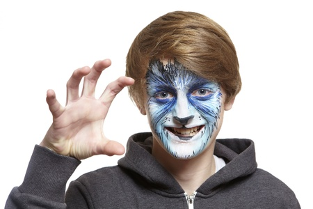 fearing: Teenage boy with face painting wolf growling on white background