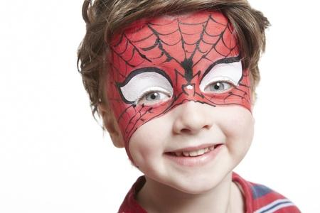painting face: Chico joven con pintura de la cara de spiderman sonriente sobre fondo blanco