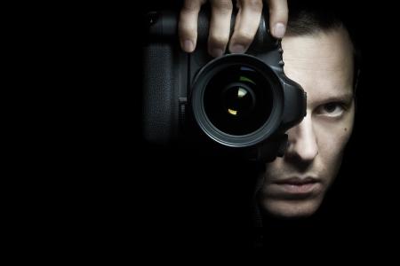 operates: Fotografo di foto con la fotocamera su sfondo nero