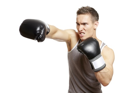 Muscular young man with boxing gloves throwing a punch in sports outfit on white background