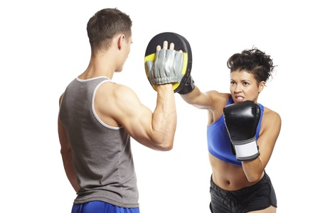 Young man and woman boxing sparring in sports outfits on white background