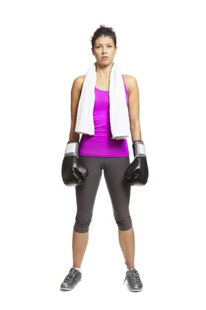 Young woman in sports outfit wearing boxing gloves and towel on white background photo