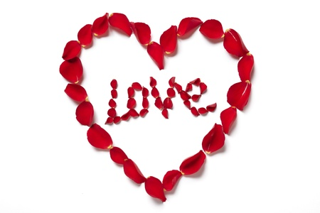 romantically: Red rose petals in heart shape spelling love on white background