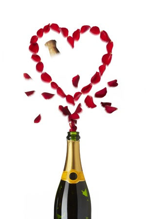 Heart shaped red rose petals popping out of champagne bottle on white background photo