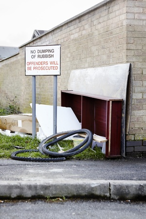 abandoning: Abandoned garbage left next to no dumping of rubbish sign on street