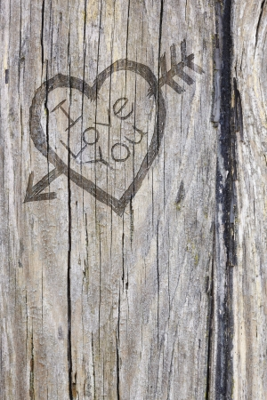 arrow wood: Love heart and arrow graffiti carved into old wood Stock Photo