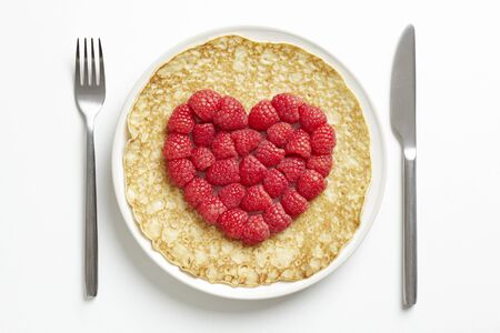 pancake: Pancake on plate with love heart shape on white table Stock Photo