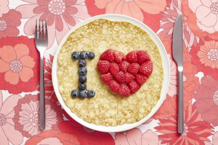 Pancake on plate with love heart shape on table