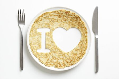 shrove tuesday: Pancake on plate with love heart shape cut out on white table