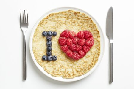 Pancake on plate with love heart shape on white table Stock Photo