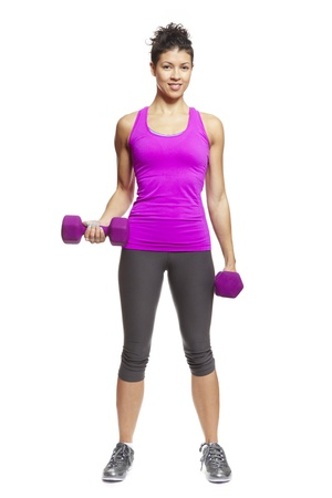 self confidence: Young woman exercising in sports outfit holding dumbbells on white background