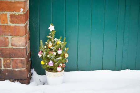 Small decorated christmas tree abandoned in snowy street Stock Photo - 18004644