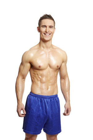 Muscular young man flexing muscles in sports outfit on white background photo