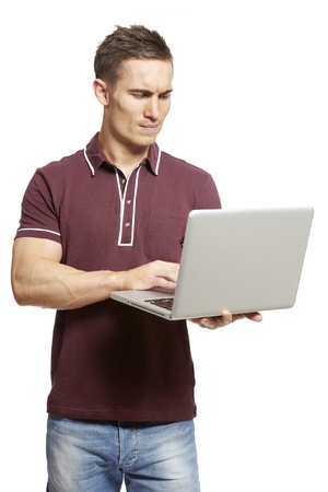 Young man using laptop on white background looking confused photo