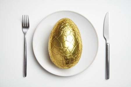 Chocolate easter egg on plate with knife and fork photo