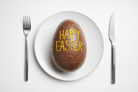 dark chocolate: Chocolate easter egg on plate with knife and fork