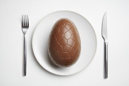 Chocolade paasei op plaat met mes en vork