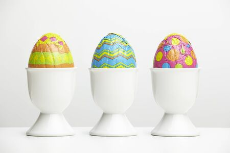 3 month: Chocolate easter eggs in egg cups on white table