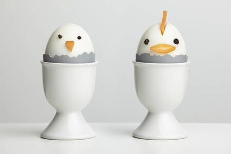Boiled egg chickens in egg cups on white table top