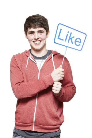 Teenage boy holding a social media sign smiling on white background photo