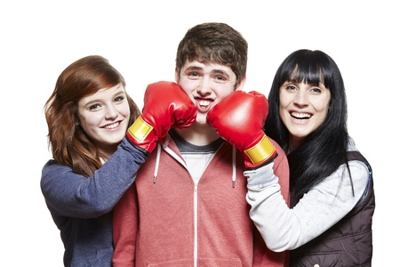 disagreeing: Teenage siblings fighting with boxing gloves on white background