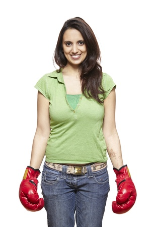 caucasian ethnicity: Young woman wearing boxing gloves smiling on white background
