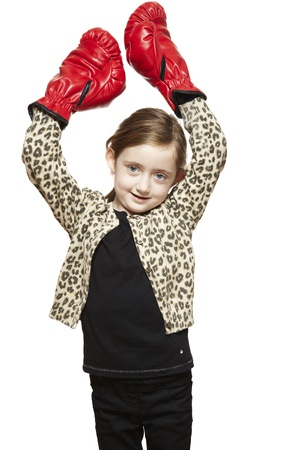 Young girl wearing boxing gloves smiling on white background photo